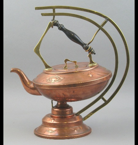 An Arts & Crafts brass and copper kettle on associated stand
