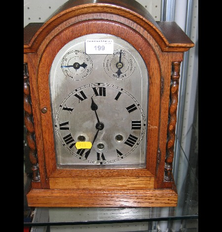 An oak cased mantel clock with chiming movement